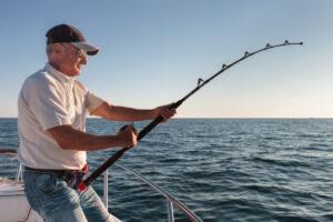 Fisherman reeling in a fishing pole on a boat in the Keys