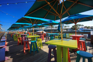 Sunset pier in Key West with colorful wooden tables, and umbrellas